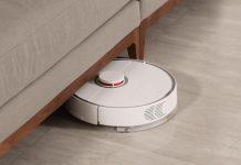 Aspirador robot no chão meio debaixo de um sofá