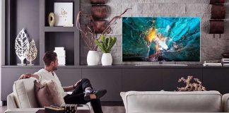 Senhor na sua sala de estar a ver televisão colocada num móvel