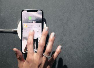 Mão a mexer em iPhone em cima de um carregador sem fios, a fazer carregamento sem fios