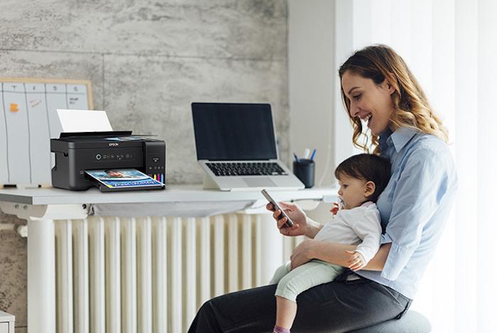 Mulher com bebé ao colo e secretária com computador portátil e impressora ecotank em segundo plano
