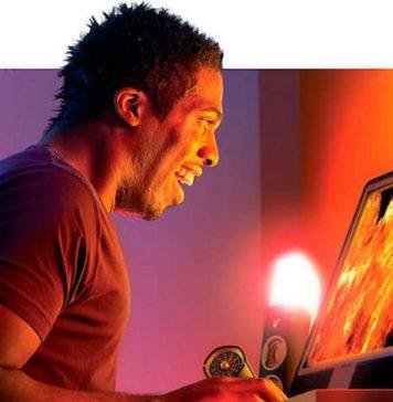 Rapaz a jogar num monitor para jogos de consola com luz quente e rapariga atrás