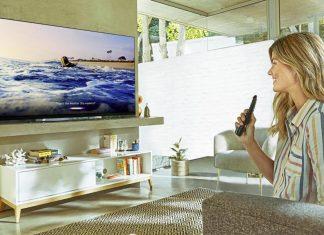 Senhora com comando na mão a ver televisão 8k