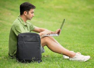 Rapaz sentado na relva com um computador portátil e mochila de portátil