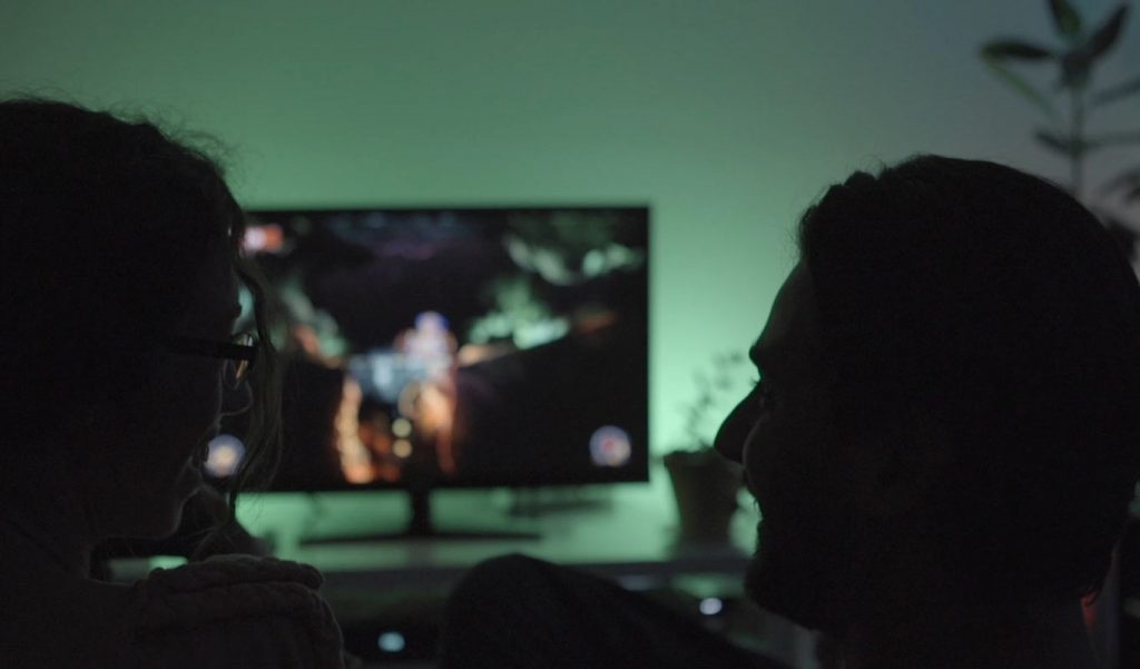 Homem e mulher de perfil em pouca luz com ecrã ou monitor para jogos no meio