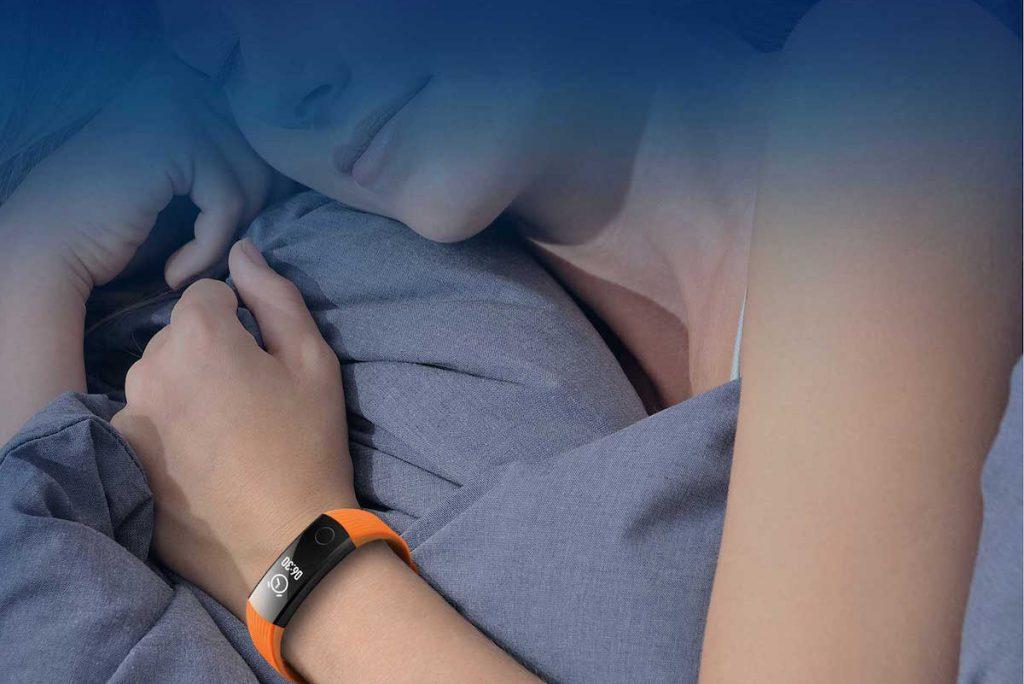Mulher a dormir com pulseira monitor de atividade no pulso