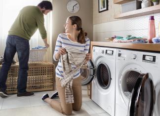 Casal a tratar da roupa usando máquina de lavar e de secar