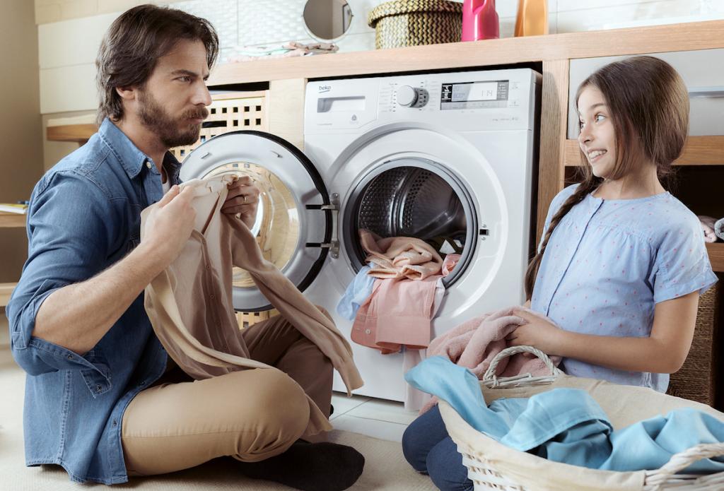 Pai e filha a tratar da roupa usando máquina de lavar