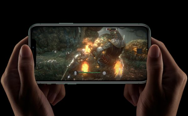 Jogo no iPhone 11 e mãos a segurar no smarpthone