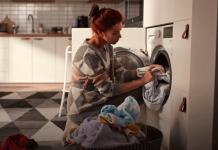 Senhora a colocar a sua roupa numa máquina de lavar ou de secar roupa