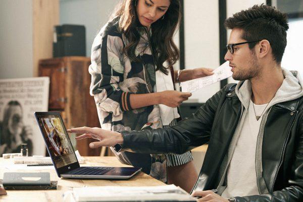 Estudantes a discutar algo em frente a computador portátil, um equipamento de tecnologia para a Universidade