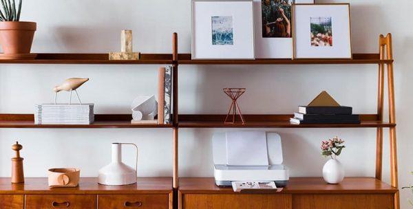Estante com vários elementos de decoração bonitos e uma impressora lá no meio
