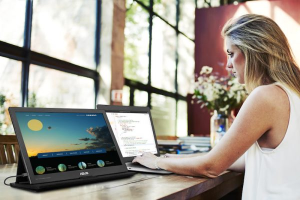 Senhora de perfil com computador portátil ligado a monitor extra em secretária