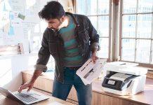 Senhor de pé a trabalhar com computador portátil e impressora atrás