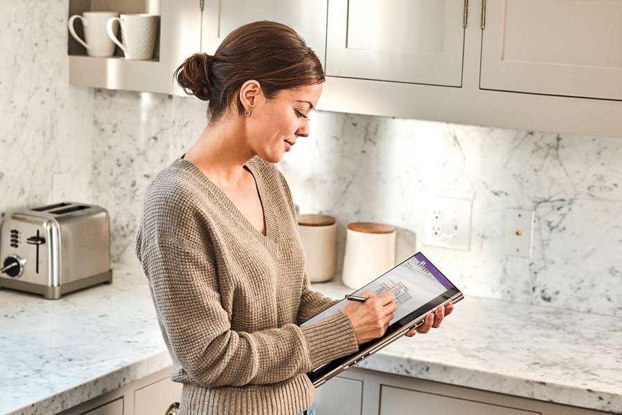 Senhora numa cozinha a usar um tablet com a Windows Ink