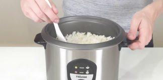 Panela elétrica ou arrozeira com arroz dentro e mãos a mexer