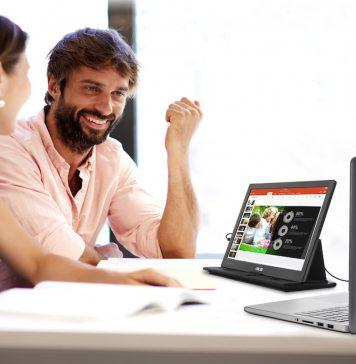 Senhor de frente e mulher de costas com computador portátil ligado a um monitor extra
