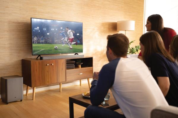 Grupo de amigos a ver desporto no televisor com soundbar