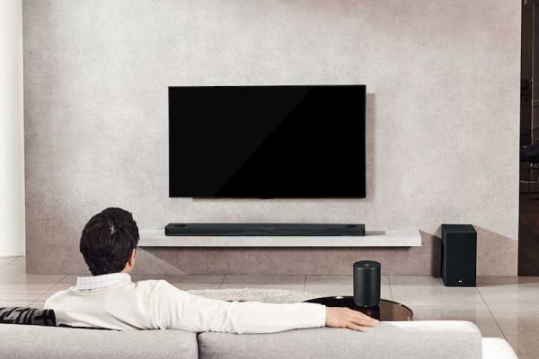 Senhor de costas na sua sala com televisor e soundbar