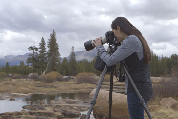 Rapariga a fotografar paisagem com câmara e tripé num mundo da fotografia profissional