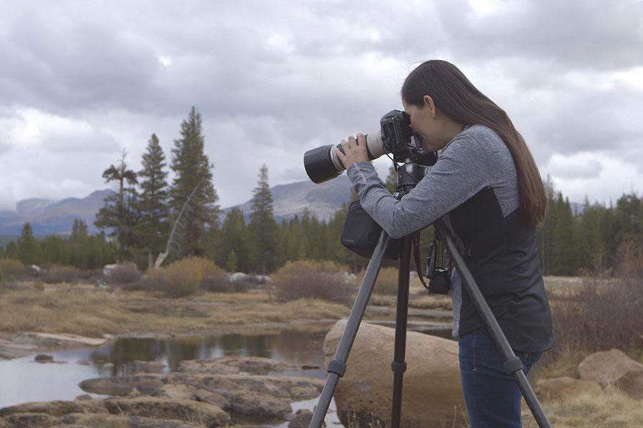 Rapariga a fotografar paisagem com câmara e tripé
