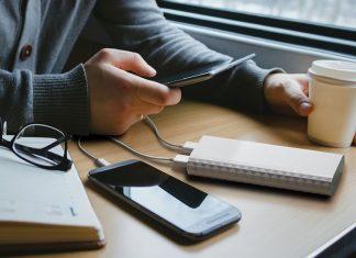 Mão a segurar em smartphone que está a carregar com uma powerbank em cima de secretária com outros objetos
