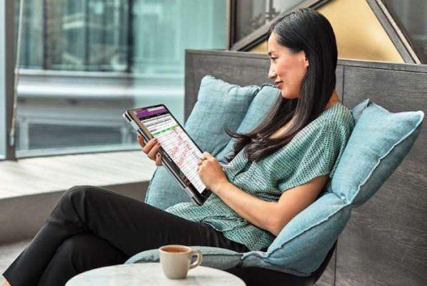 Senhora sentada num sofá a trabalhar num tablet com a Windows Ink