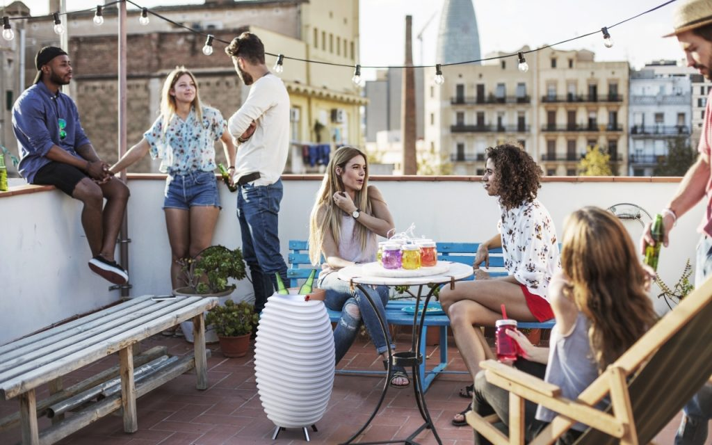 Grupo de amigos no terraço a disfrutar da vida e uma Kooduu com duas garrafas dentro no centro