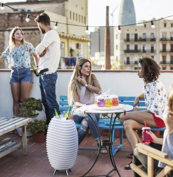 Grupo de amigos no terraço a disfrutar da vida e um Synergy da Kooduu com duas garrafas dentro no centro