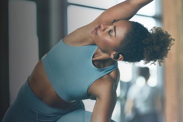 Menina a fazer exercício e a usar os auriculares PowerBeats Pro