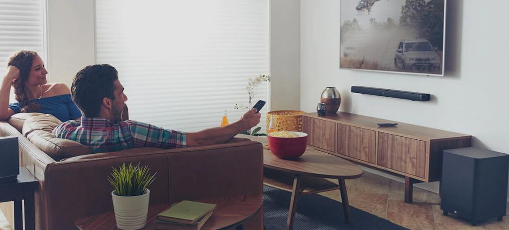 Casal de perfil a aperciar a sua TV com barra de som