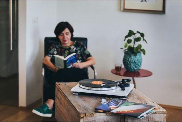 Rapaz a ler com um gira-discos em cima da mesa