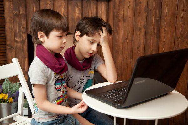 Crianças a aprender em casa através de um portátil